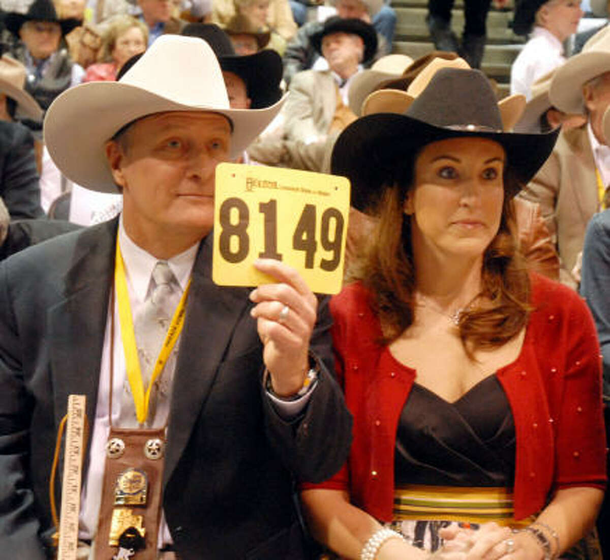 Jim Winne raises the bid during the reserve champion auction while his wife Lynda looks on.