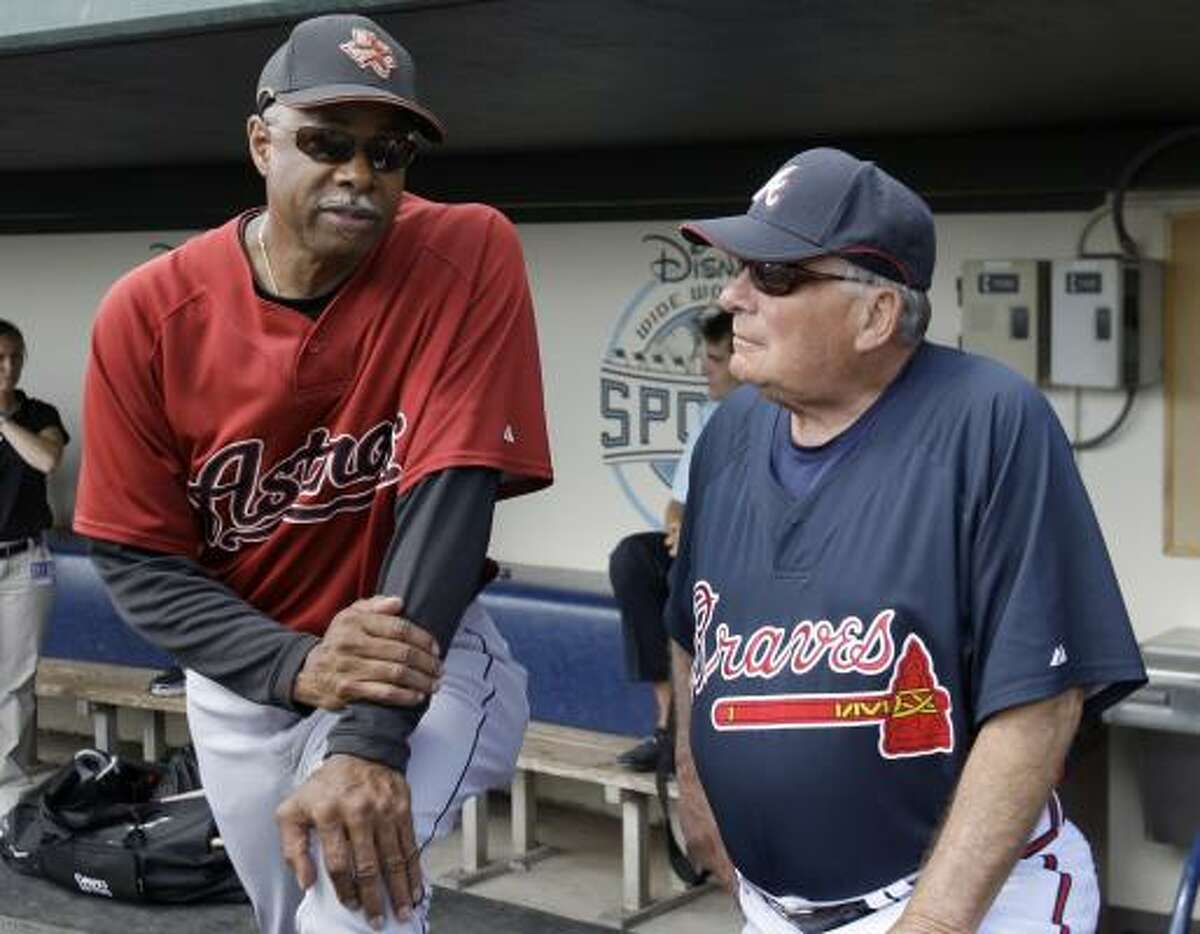 Astros manager Cecil Cooper, left, talks with Atlanta Braves manager Bobby Cox, right, before the start the game.