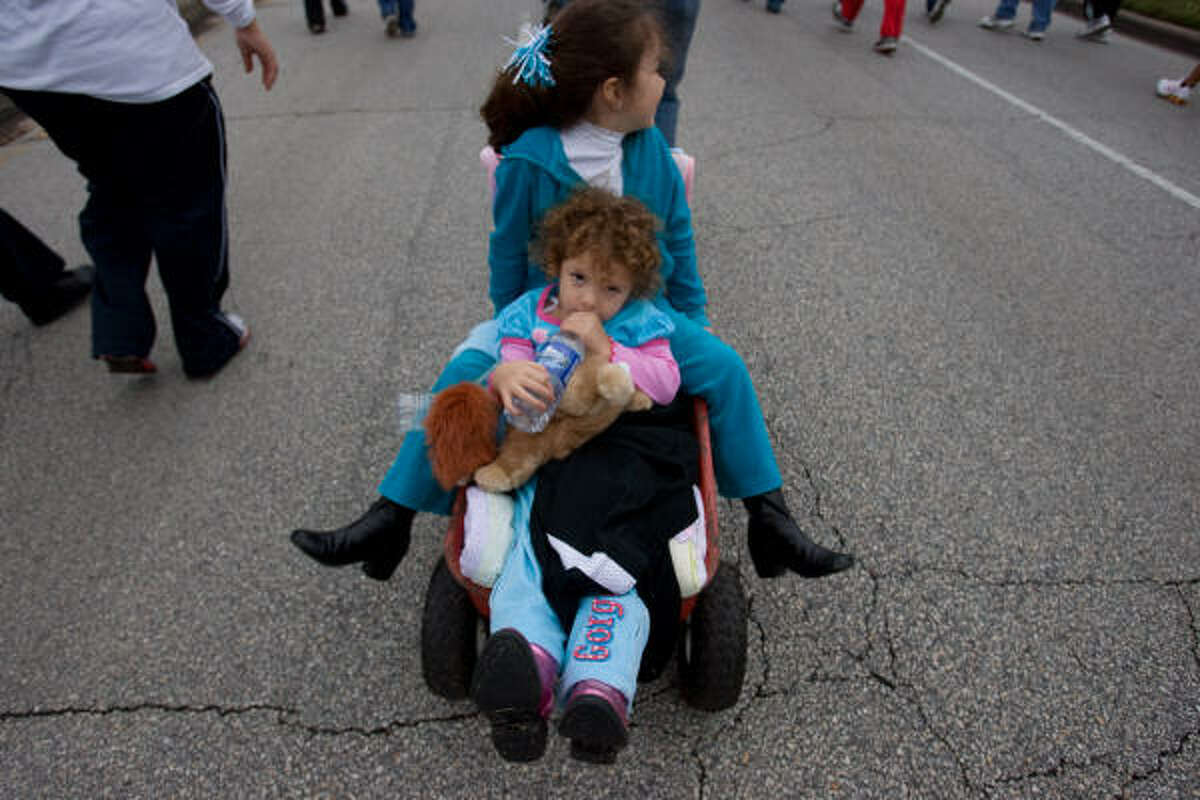 Carmella Villarreal, 3, front, and her sister Isabella, 5, are pulled in a wagon by their mother Marigrace Villarreal at the 20th Annual AIDS Walk Houston on Sunday.
