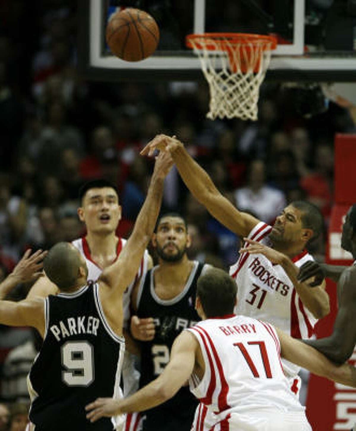 Spurs guard Tony Parker (9) has a jumpball against Shane Battier (31) late in the second half.