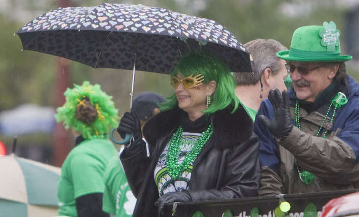 Mary and John Pennington wave while riding on a trailer during the 50th annual Houston St. Patrick's Day Parade downtown on Saturday.