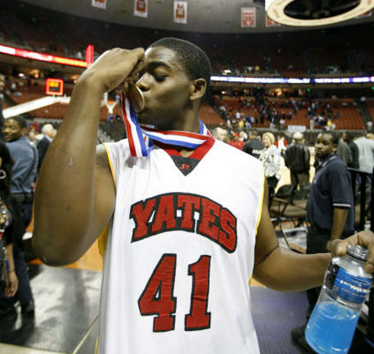 Yates center Christian Hill (41) kisses his medal after beating Dallas Kimball 94-78 in the 4A UIL Boys' Basketball State Championship.