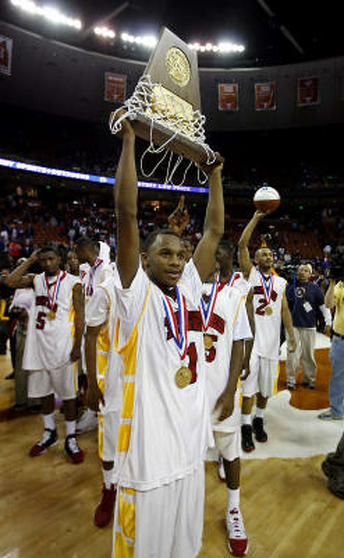 Yates guard Darius Gardner (1) holds up the 4A trophy