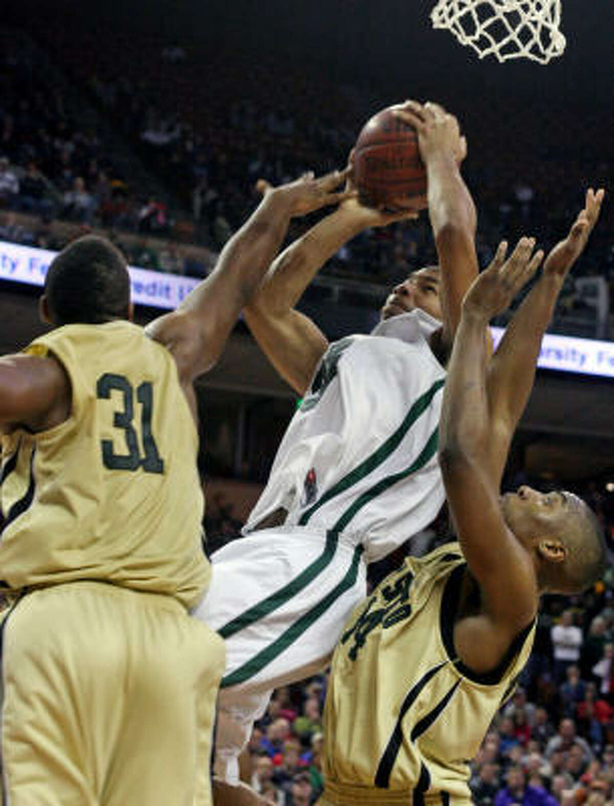 DeSoto's Darius Terrell, right, and Evan Washington (31) defend against Strake Jesuit's Joey Brooks, center.