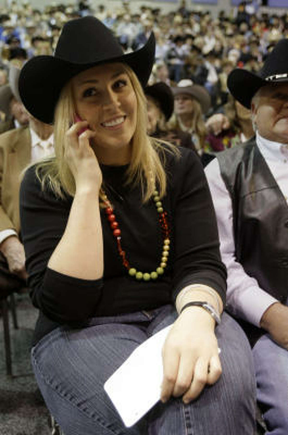 Laura McIngvale talks on the phone to her dad, Jim McIngvale, owner of Gallery Furniture, as she bids on the Grand Champion during the Junior Market Steer Auction at Reliant Arena Sales Pavilion at the Houston Livestock Show and Rodeo on Saturday, March 14, 2009, in Houston.