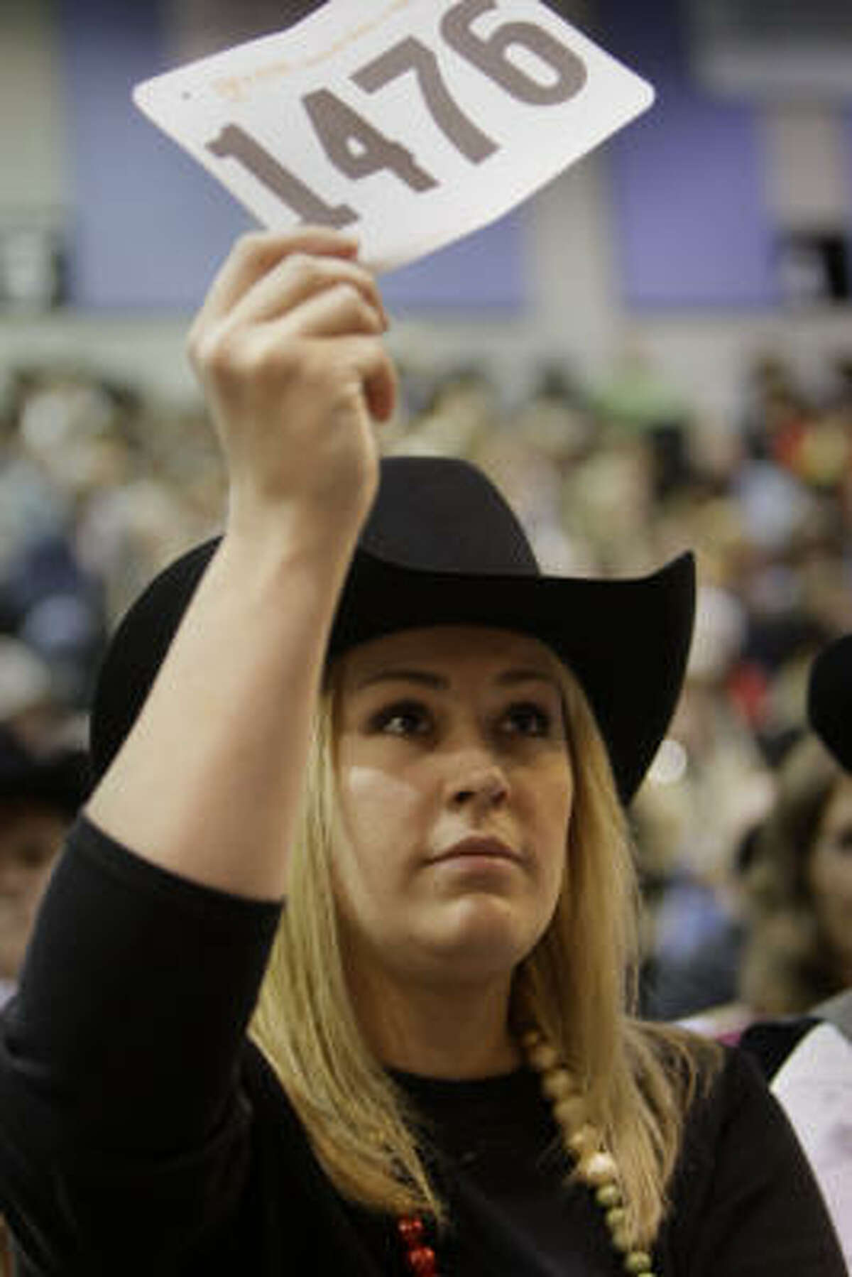 Laura McIngvale bids on the Grand Champion during the Junior Market Steer Auction at Reliant Arena Sales Pavilion at the Houston Livestock Show and Rodeo on Saturday, March 14, 2009, in Houston.