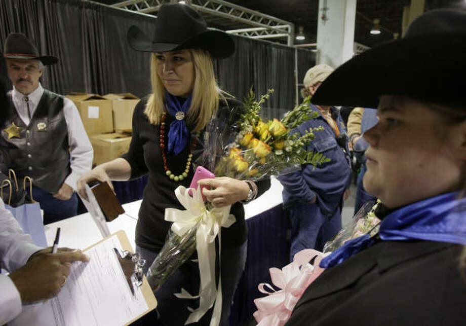 "Laura McIngvale and her best friend, Lindsey Leggett deal with paperwork after McIngvale won the bid on the Grand Champion during the  Junior Market Steer Auction at Reliant Arena Sales Pavilion at the Houston Livestock Show and Rodeo on Saturday, March 14, 2009, in Houston.  McIngvale said she's a vegan, adding, ""If they would let me keep it, I would have it in my backyard."" Photo: Melissa Phillip, Chronicle"