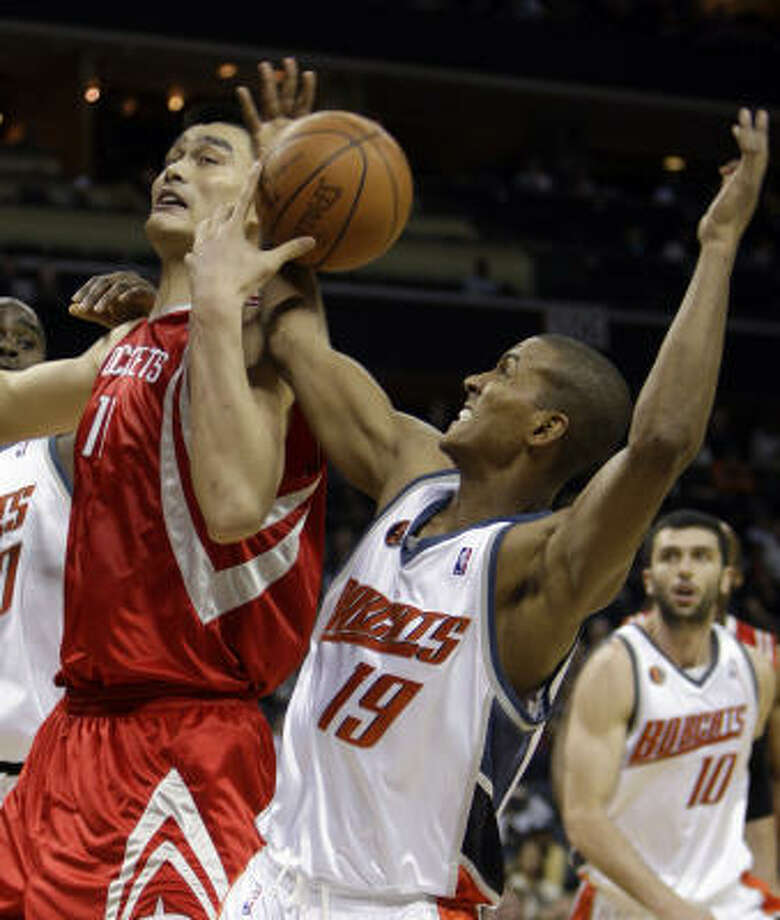 Yao Ming, left, and Bobcats guard Raja Bell (19) fight for a rebound during the second half. With the shot clock down to its final seconds, Yao nailed the second 3-pointer in his 10-career attempts, putting the Rockets ahead 83-77 with 2:12 left. Photo: Chuck Burton, AP