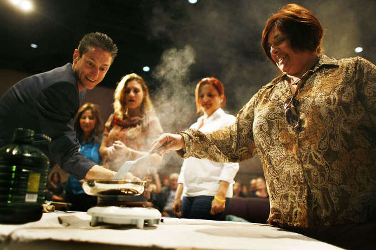 Kevin Cross (L) helps Ileana Garcia cook several of her credit cards over a hot plate during a sermon about faith-based financial management at the Miami Vineyard Community Church.
