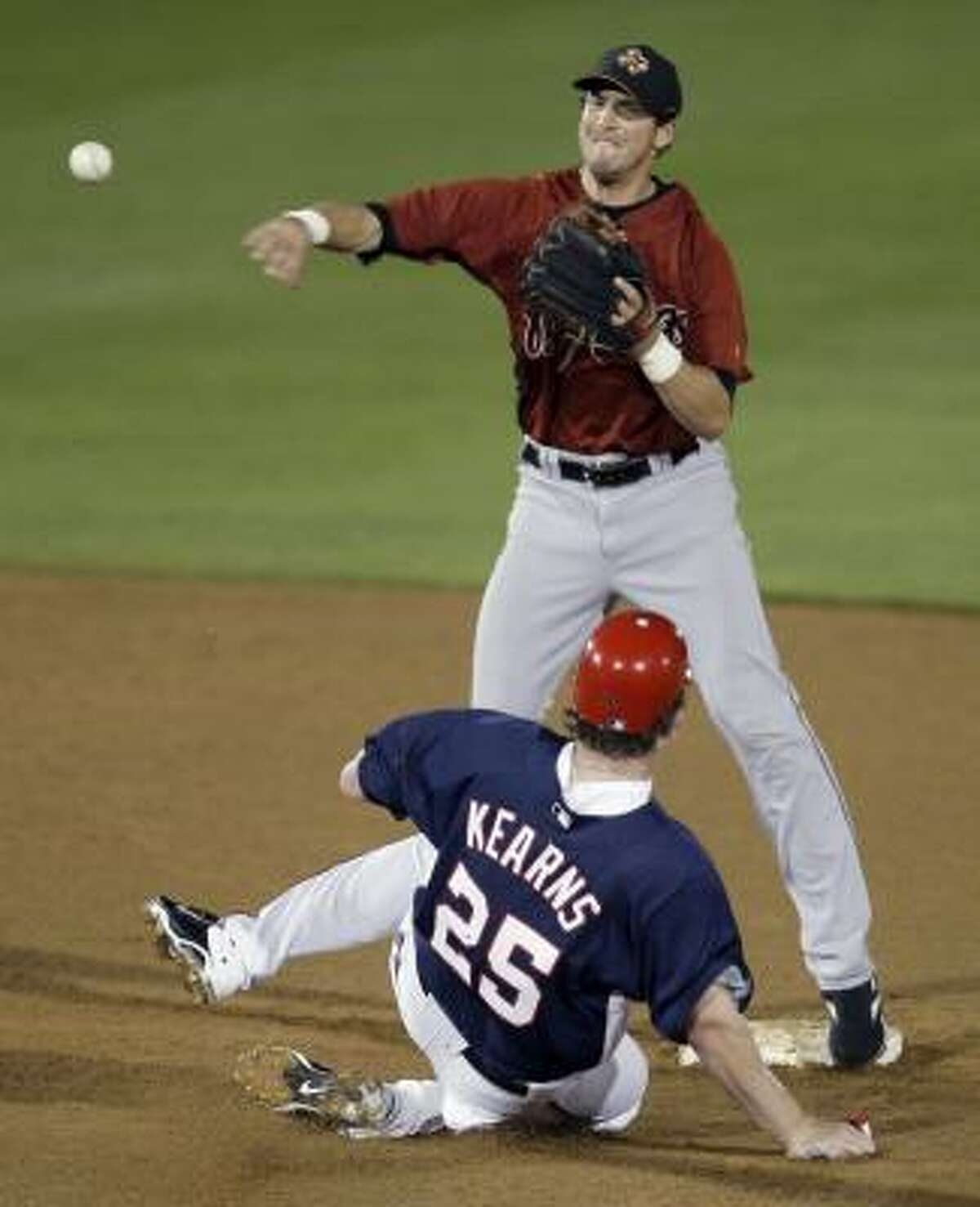 Astros shortstop Tommy Manzella throws to first after forcing out Washington Nationals outfielder Austin Kearns at second during the third inning.