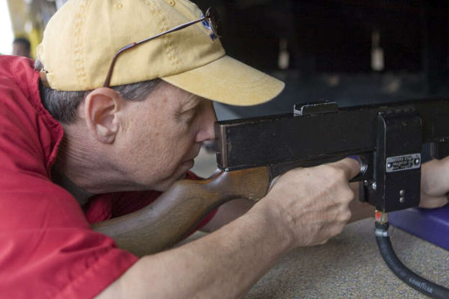 "Ken Hoffman tries to shoot a star out of a card  in the ""Shoot Out Stars"" booth. Photo: Steve Campbell, Houston Chronicle"