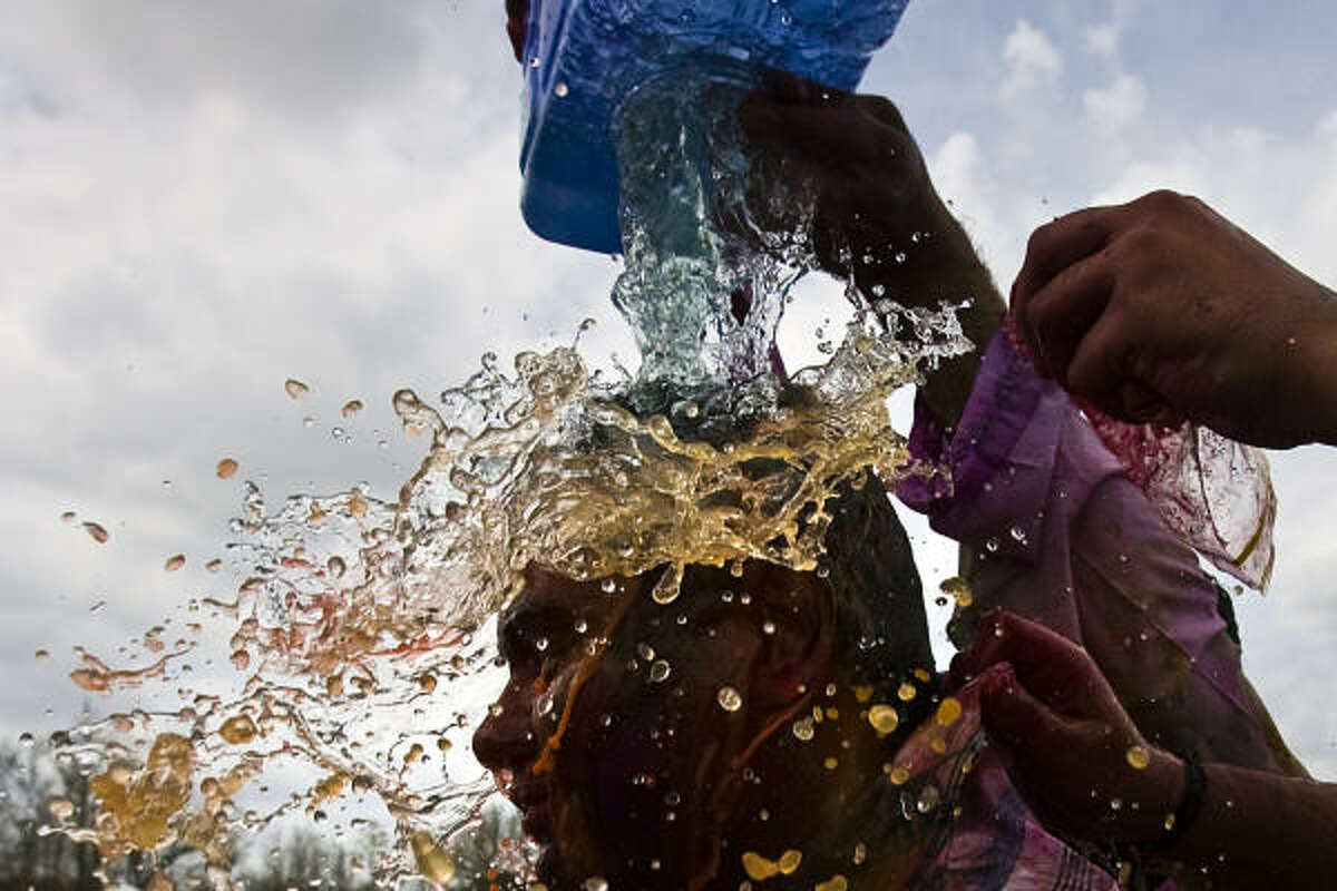 A reveler is doused with colored water and dye during the festival which celebrates spring and various events in Hindu mythology.