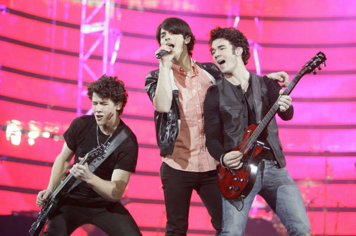 From left, Nick Jonas, Joe Jonas and Kevin Jonas perform at the Houston Livestock Show and Rodeo Sunday.