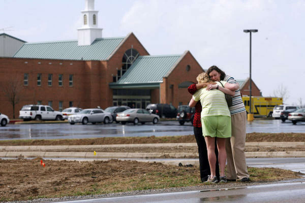 Mourners comfort each other near the First Baptist Church in Maryville, Ill., where the church pastor was gunned down on Sunday.