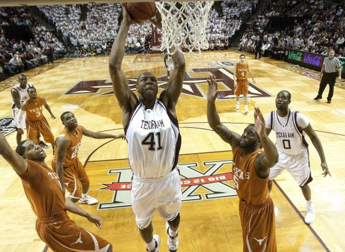 Texas A&M's Chinemelu Elonu dunks as Texas' Damion James (5) and teammates watch during the second half.