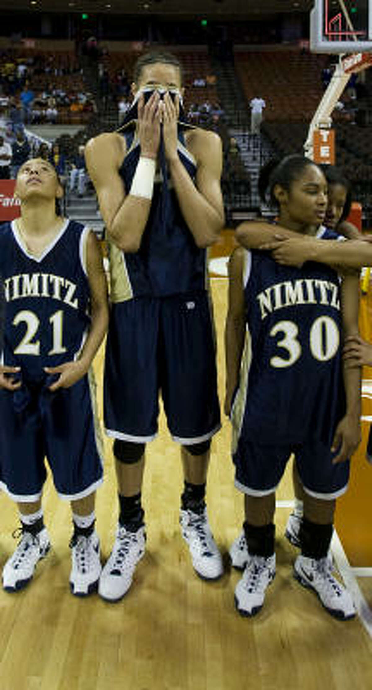 Brittney Griner and teammates Jessica Diamond (21) and Alicia Seay (30) react following Nimitz's loss.
