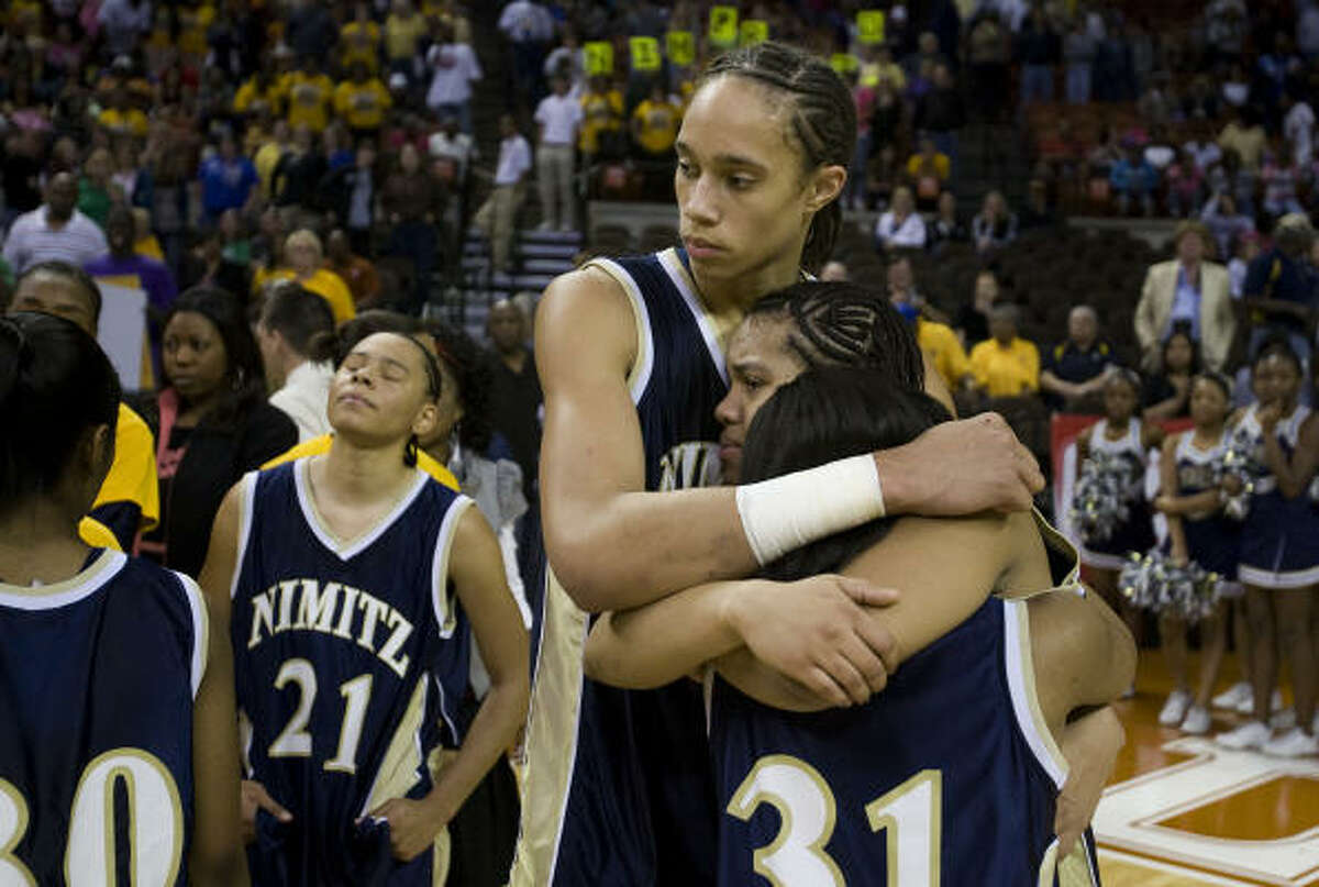 Brittney Griner hugs teammates Chrishuana Parker (32) and Kim Barnes (31) following Nimitz's loss.