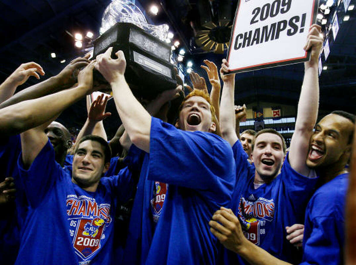 Kansas seniors Brennan Bechard, left, and Matt Kleinmann, middle, accept the trophy after the Jayhawks defeated Texas to claim their fifth straight Big 12 Conference championship.