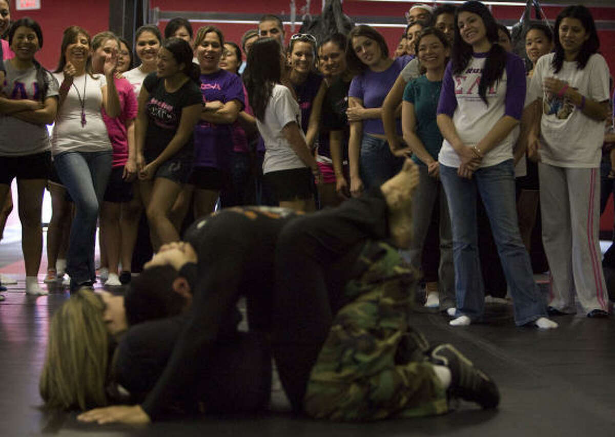 Self-defense instructors Malvin Traylor and his wife Fabiana demonstrate an attack during a self-defense class and fundraiser for Sabrina Piña at Dark Gift Combat Reality Based Martial Arts Center Saturday in Houston.