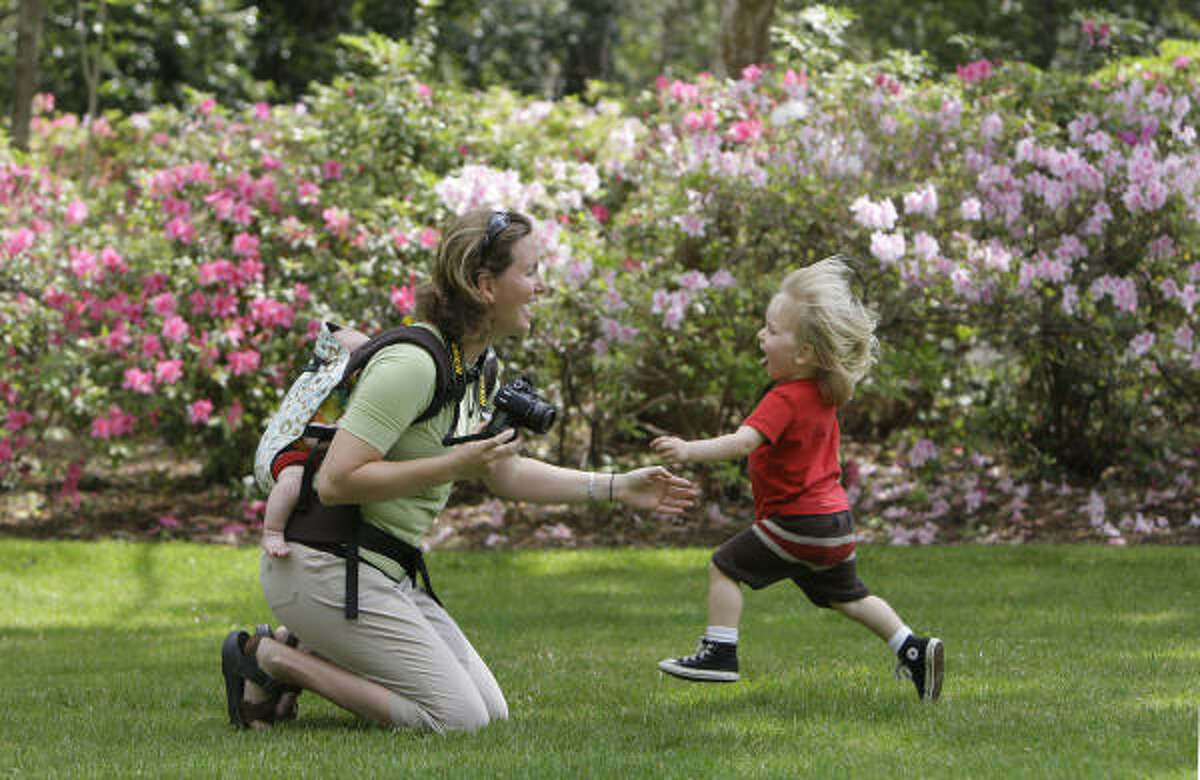 Cyndy Schaefer plays with her sons Wyatt, 3 months, and Taylor, 2, as they take photos at Bayou Bend Gardens during the River Oaks Garden Club's Azalea Trail home and garden tour on Saturday.