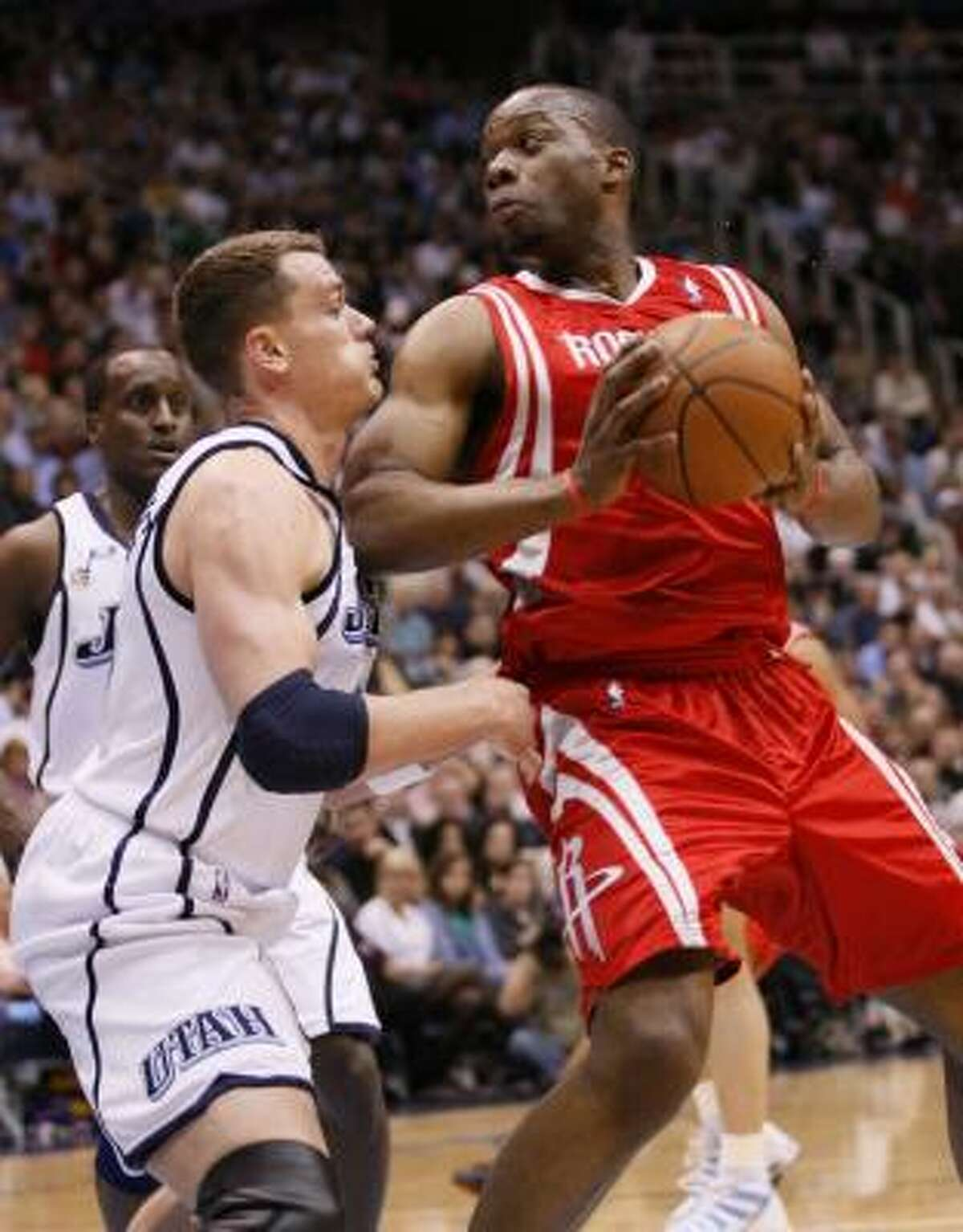 Carl Landry, right, who scored eight points, battles Jazz forward Matt Harpring for position in the second quarter.