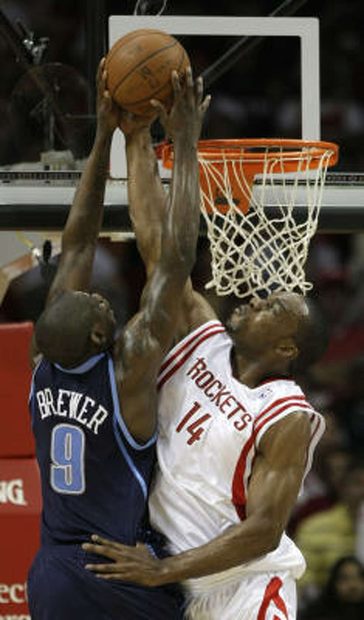 2008-09 SEASON Rockets forward Carl Landry, right, gives Ronnie Brewer a rude welcome at the rim in their first meeting of the 2008 season. The Rockets defeated the Jazz 120-115.