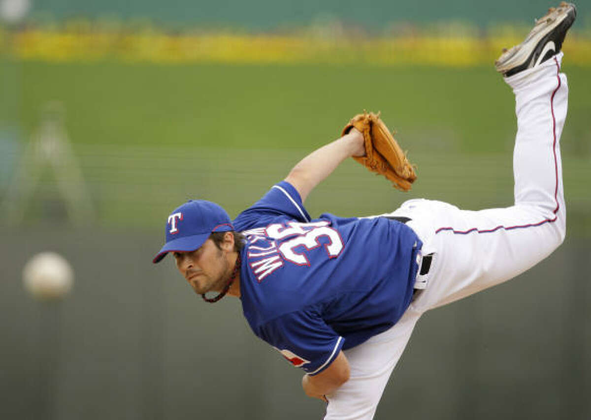 Rangers pitcher C.J. Wilson delivers a pitch during the ninth inning of game against the San Diego Padres. The Rangers won the game 4-3.