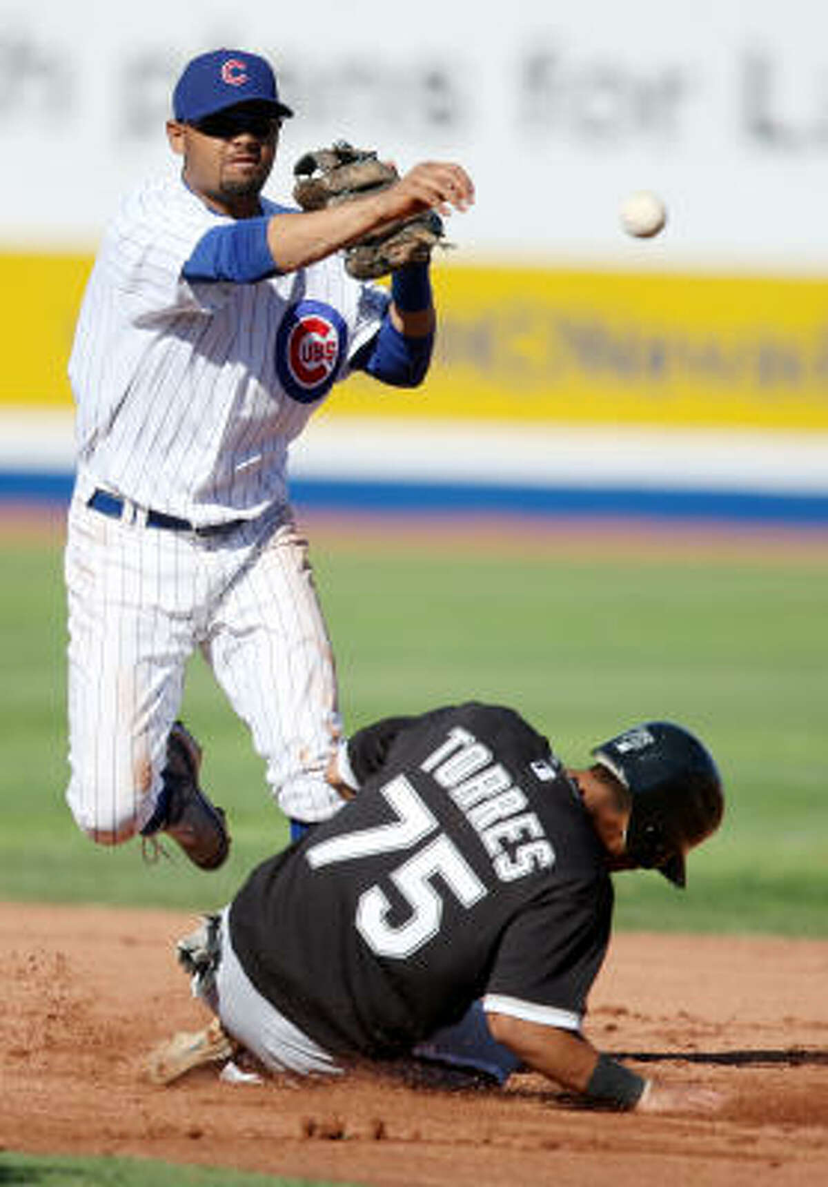 Chicago Cubs' Andres Blanco, top, throws over Chicago White Sox's Eider Torres during the fifth inning of their game.