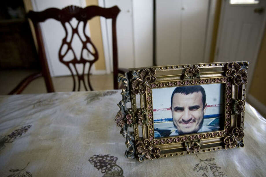 An empty chair sits at the head of the family's dining table with a photograph of Sheikh Zoubir Bouchikhi, who is facing deportation. Bouchikhi has lived in the U.S. for 11 years and has three American-born children. The popular imam's detention has angered Houston-area Muslims, who are rallying to support Bouchikhi with letter-writing campaigns, petitions and Web sites. Photo: Eric Kayne, Chronicle