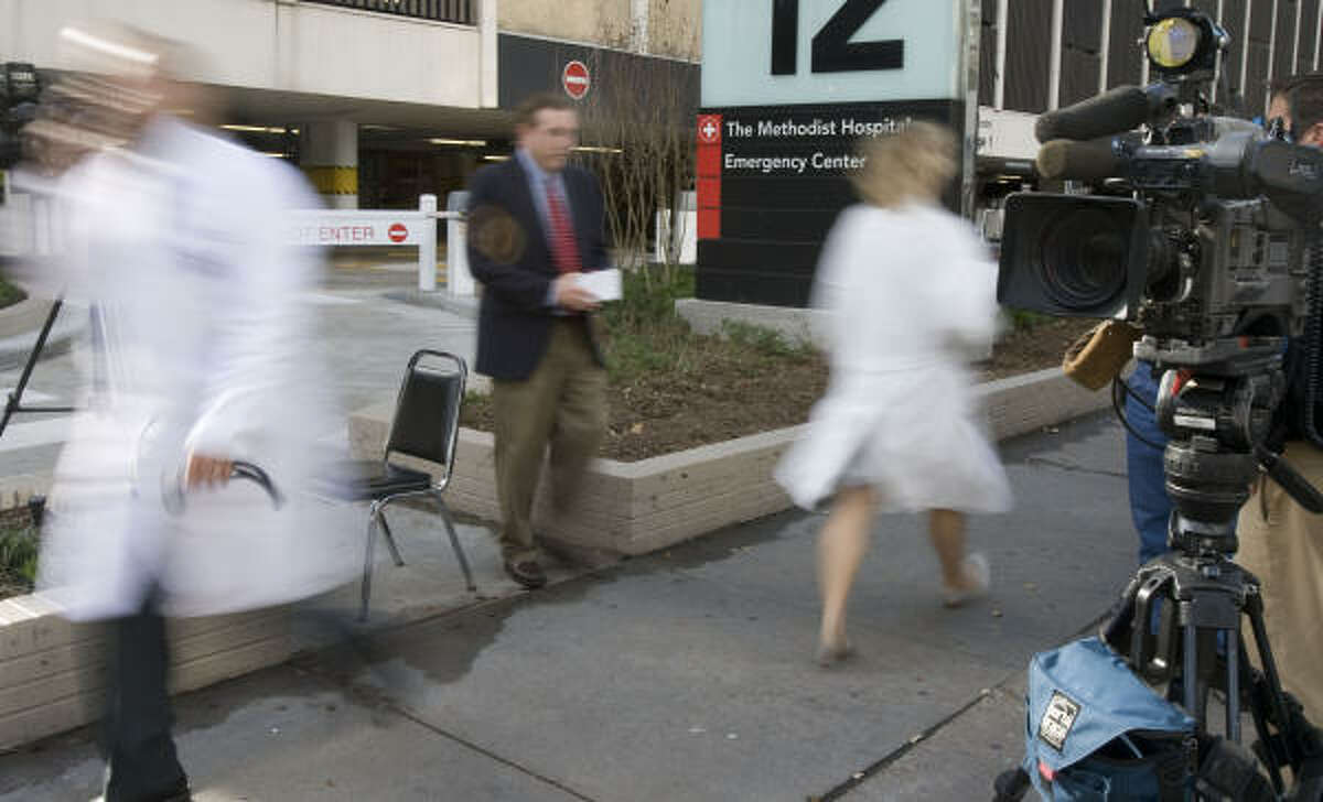 People walk past a television news crew outside The Methodist Hospital where former first lady Barbara Bush was recovering from open-heart surgery Thursday.