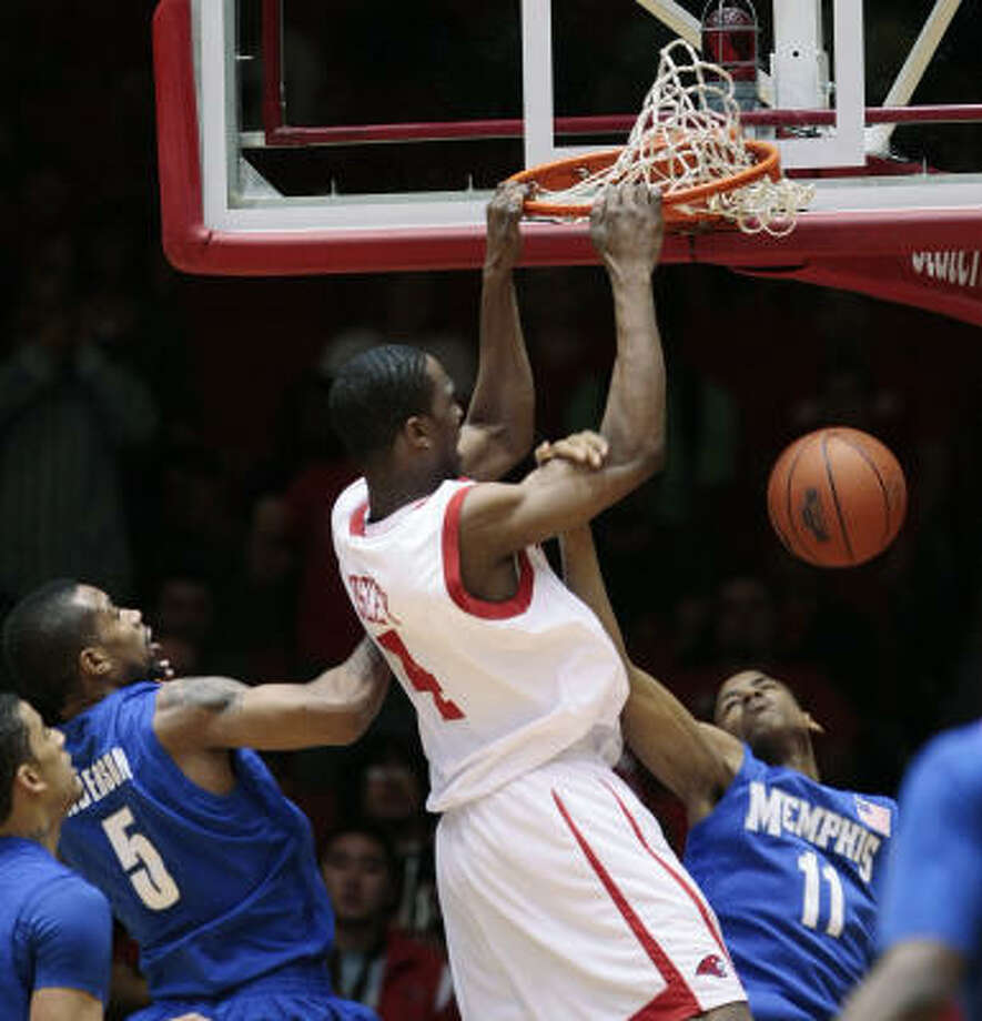 Houston's Nick Mosley dunks over Memphis' Wesley Witherspoon, right, and Antonio Anderson, left. Photo: Bob Levey, AP