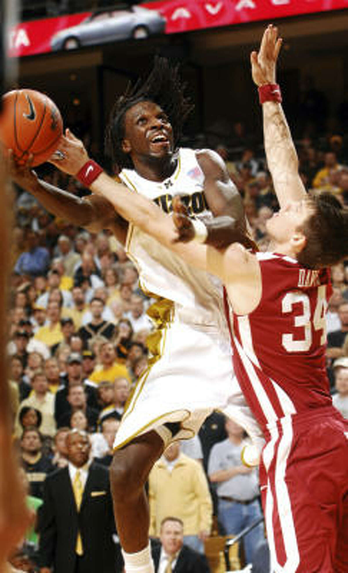 Missouri's DeMarre Carroll, left, shoots over Oklahoma's Cade Davis.