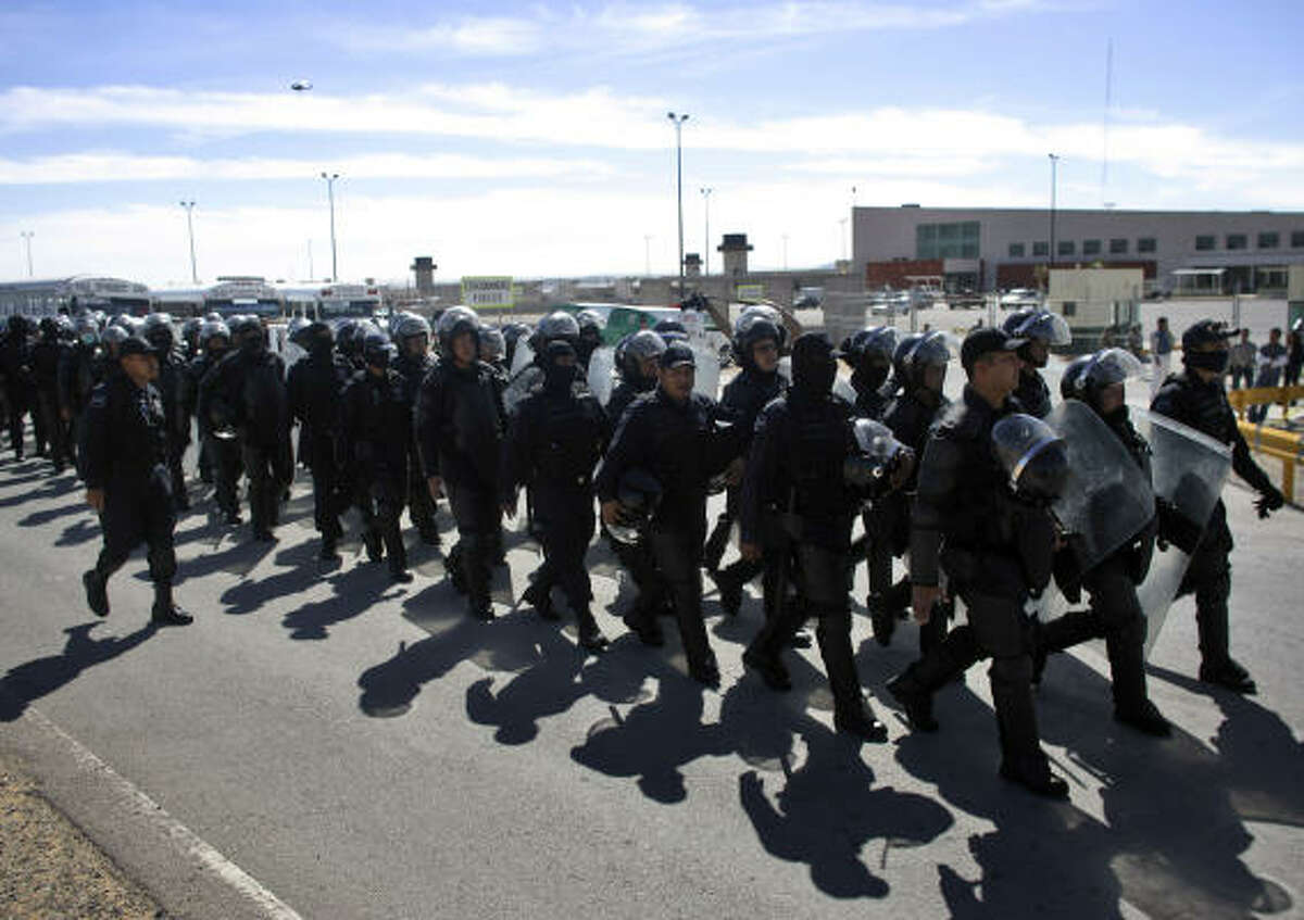 Police officers make their way into a state prison during a riot in Cuidad Juarez, Mexico, Wednesday.