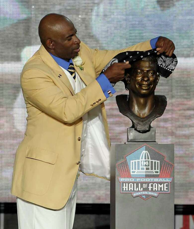 Deion Sanders puts a bandana on a bust of himself during the induction ceremony at the Pro Football Hall of Fame, Saturday, Aug. 6, 2011, in Canton, Ohio. Photo: Ron Schwane/Associated Press