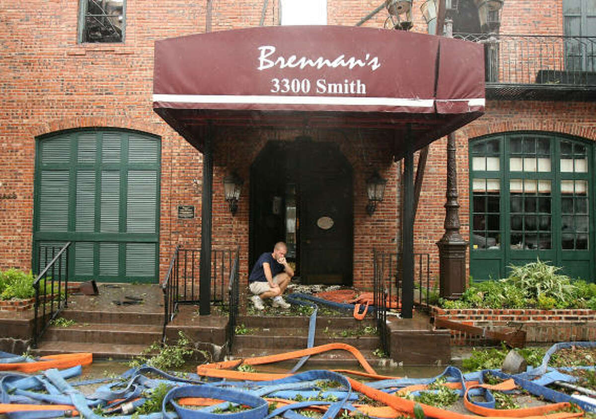 Chris Daugherty kneels in disbelief that one of his favorite restaurants, Brennen's, was lost in a fire when Hurricane Ike hit Houston.