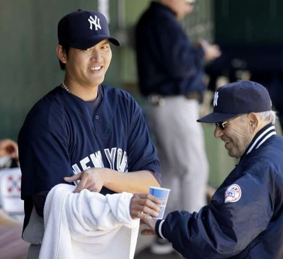 Hall of Famer Yogi Berra, who was taking in the game with the Yankees, meets with pitcher Chien-Ming Wang. Photo: David J. Phillip, AP
