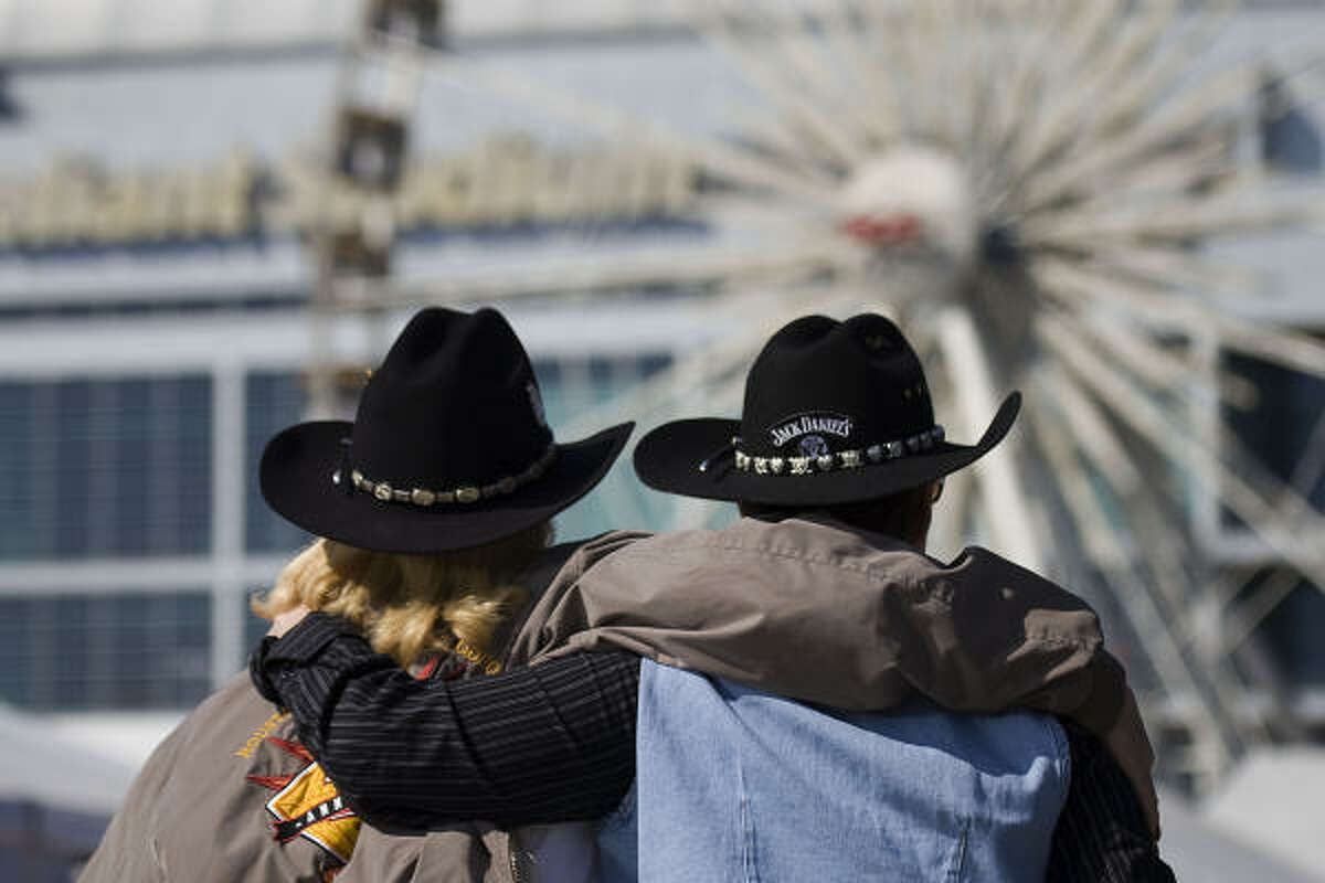 Two women take in the rodeo scene.