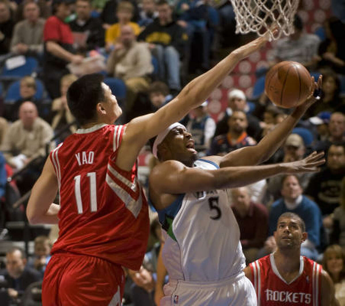 Yao Ming, left, blocks a shot under the basket by Minnesota's Craig Smith in the first quarter
