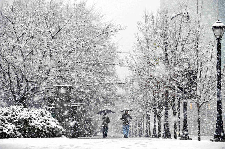 Pedestrians walk through Centennial Park in Atlanta, Ga., on Sunday as snow hit the metro area. A powerful March snowstorm blanketed much of Alabama and then marched across Georgia on Sunday. Photo: Joey Ivansco, MCT