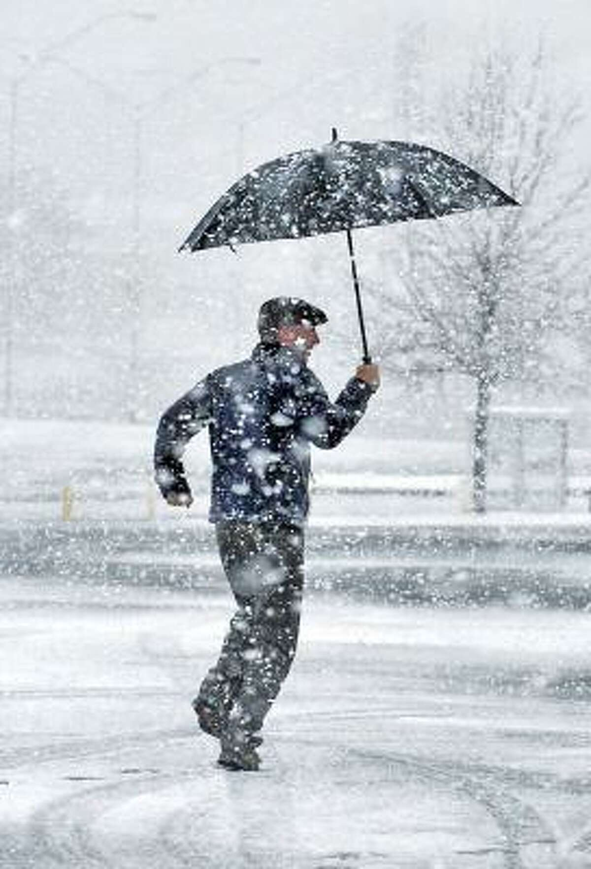 Todd Warren, visiting from Buffalo, N.Y., walks through the snow that hit Atlanta to his car after learning the 25th Annual Hunger Walk/Run event had been canceled because of the weather on Sunday.