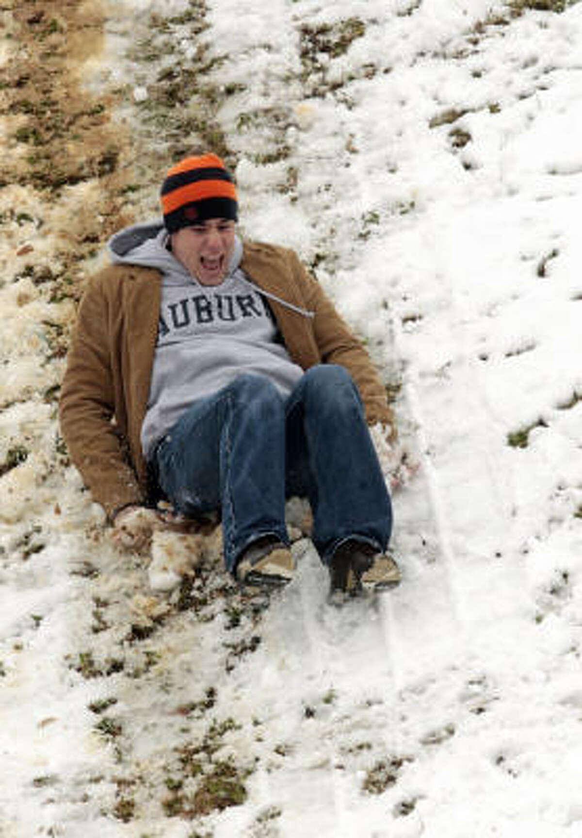 Auburn University student Patrick Duncan of Ackworth, Ga., slides down a snow covered slope on the campus in Auburn, Ala., Sunday.