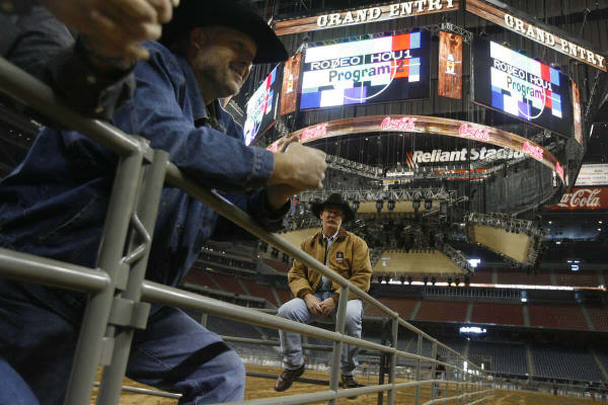 Scott Pennell, right, rests Sunday after rehearsing the setup for the Calf Scramble competition, one of the events at the Houston Livestock Show and Rodeo Sunday at Reliant Stadium.