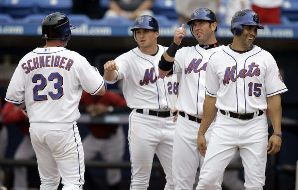 New York Mets catcher Brian Schneider (23) is congratulated by teammates Daniel Murphy (28), Ryan Church and Carlos Beltran (15) after hitting a grand slam.