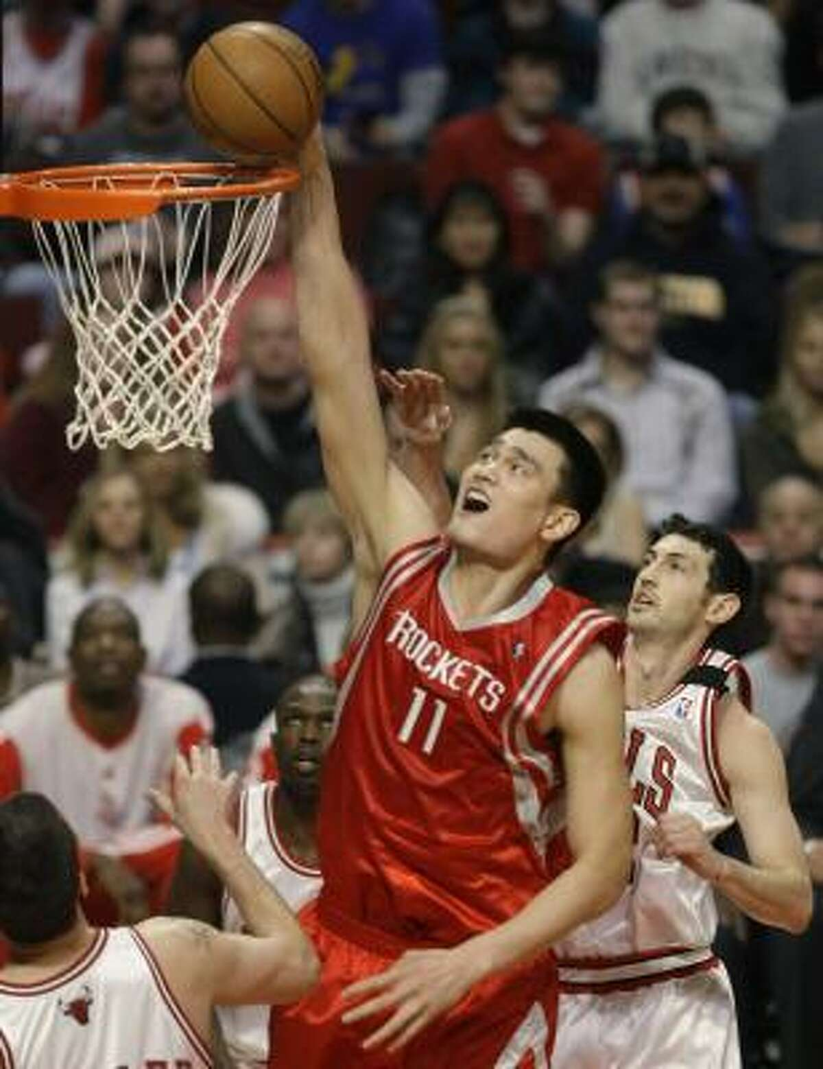 Yao Ming gets to the basket with Bulls guard Kirk Hinrich, right, trailing on the play in the first half.