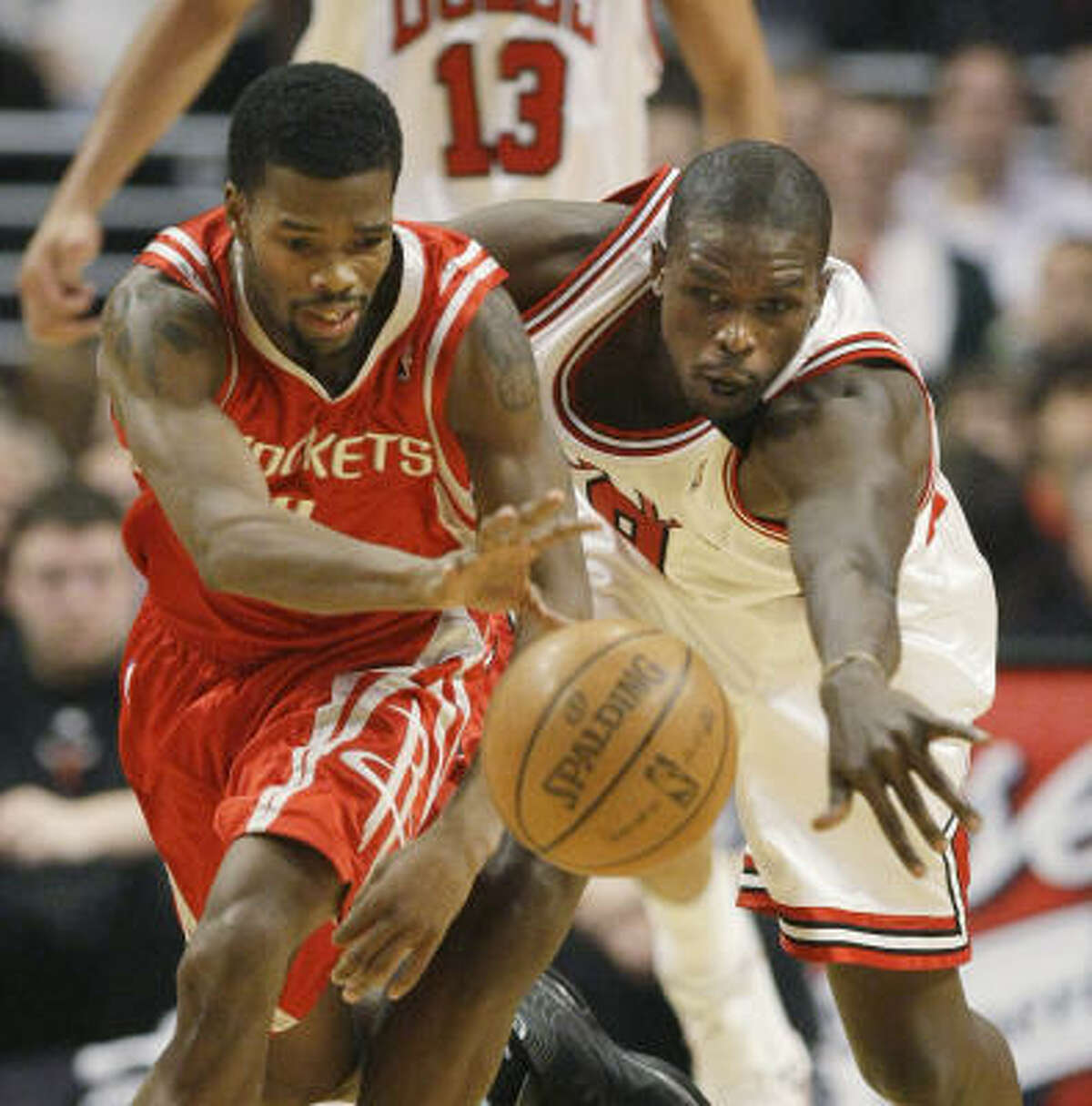 Aaron Brooks, left, battles Bulls forward Luol Deng for a loose ball in the first half.