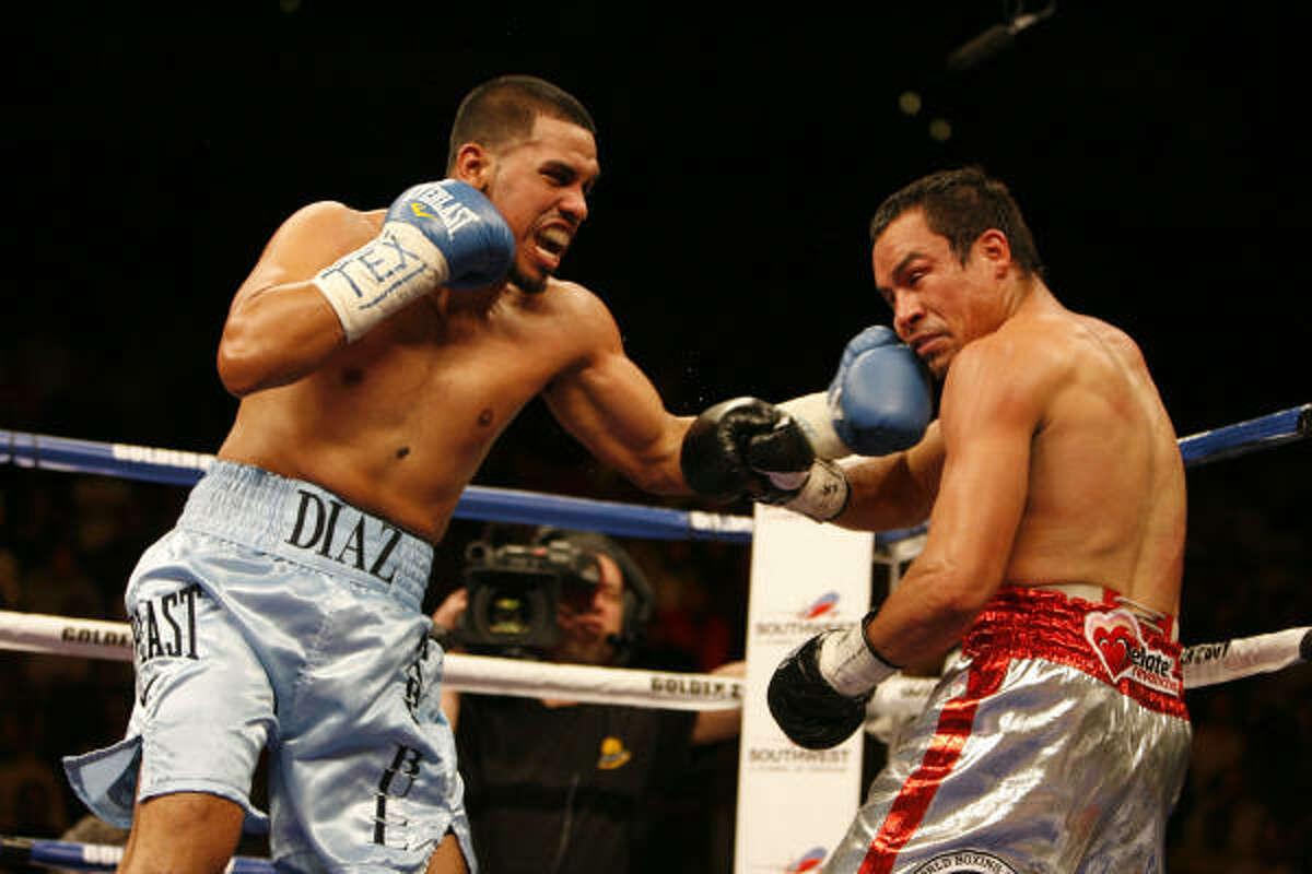 Juan Diaz, left, catches Juan Manuel Marquez with a left to the chin.