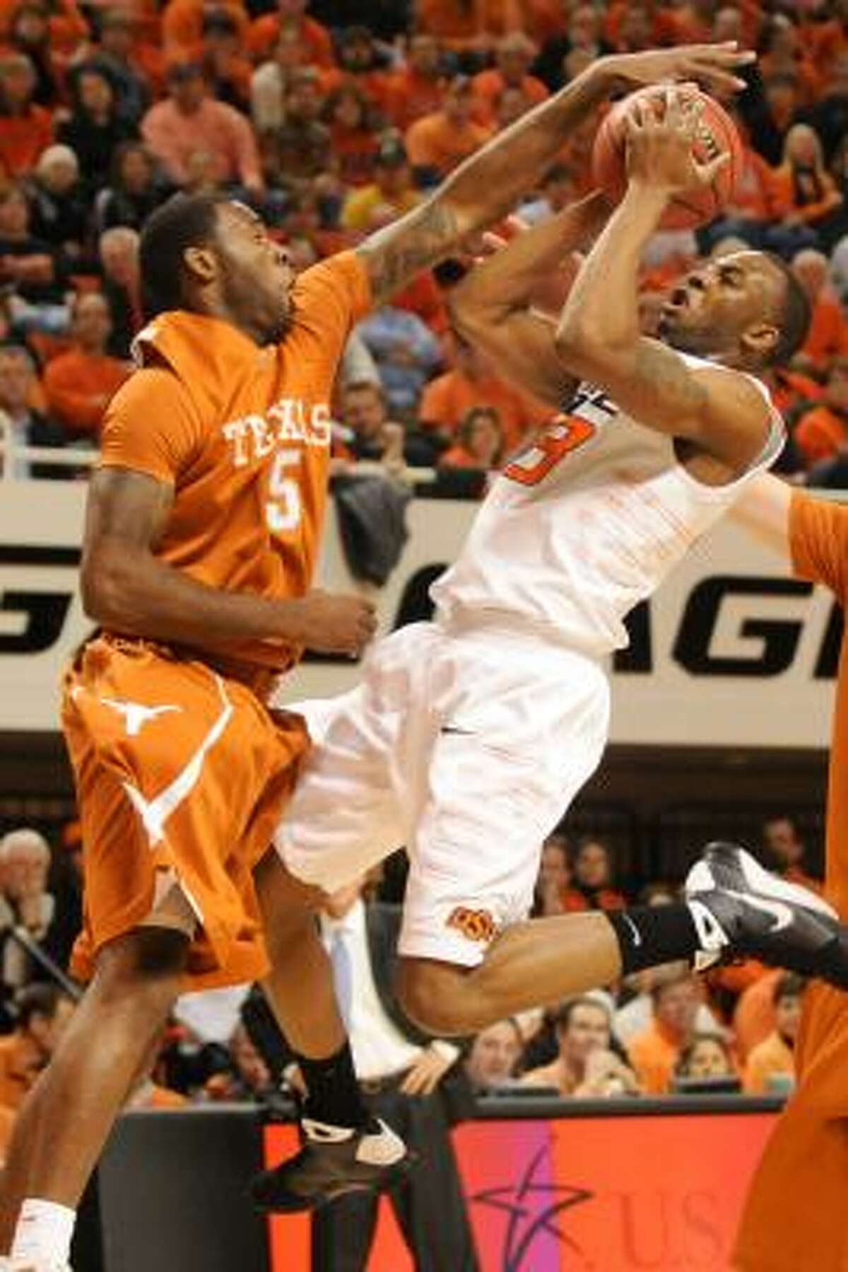 Texas forward Damion James, left, blocks the shot of Oklahoma State guard James Anderson.