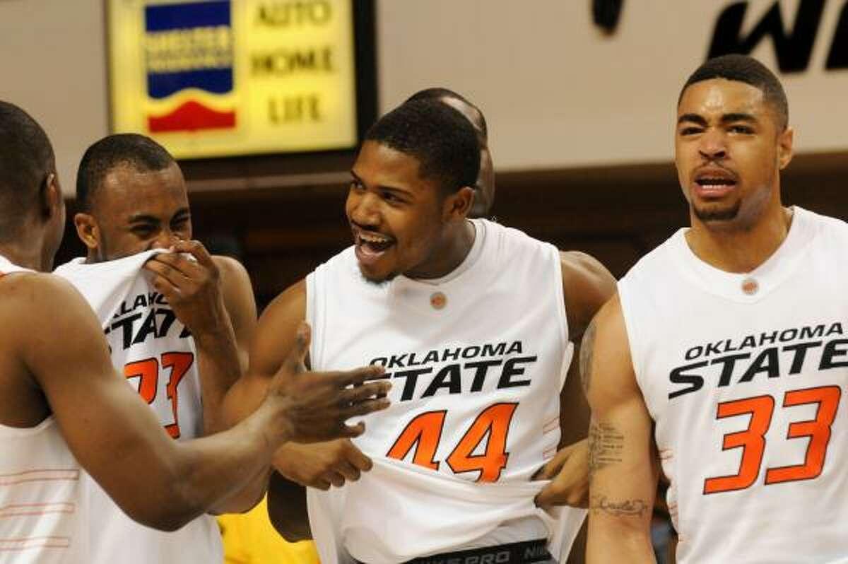 Oklahoma State's James Anderson (23), Malcoln Kirkland (44), and Marshall Moses (33) celebrate their 68-59 win over No. 25 Texas.