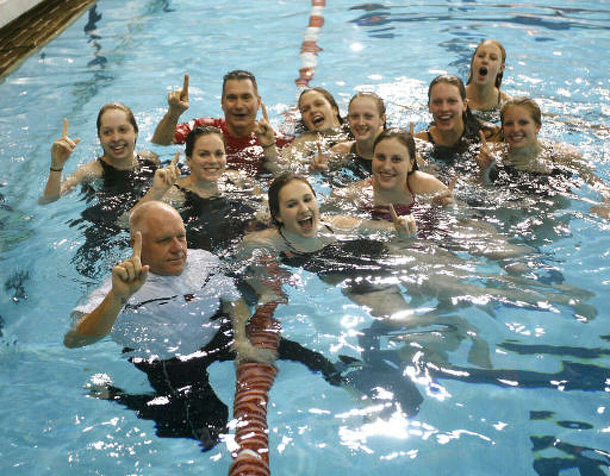 The Woodlands swimmers with school principal, Gregg Colschen, front left, and head coach, Kent Kirchner, back left, in the pool after winning the Girls' team standings.