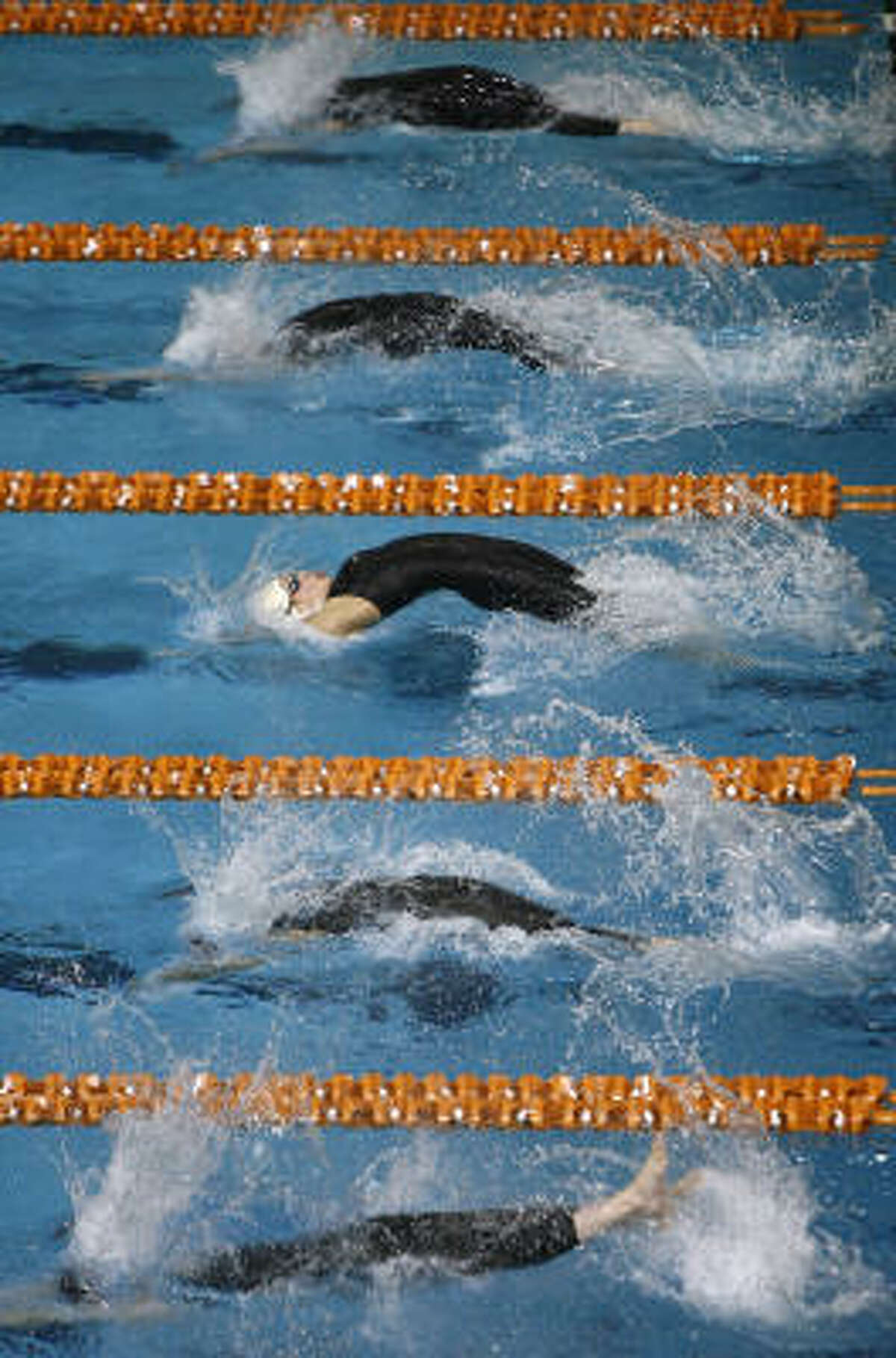 Jillian Vitarius of Humble Kingwood, third from top, takes off on the start of the Girls' 100-yard backstroke at the Jamail Texas Swimming Center in Austin.